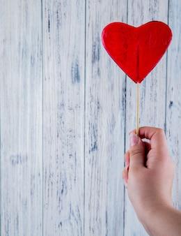 Vista superior copia espacio mujer sostiene piruleta en forma de corazón rojo