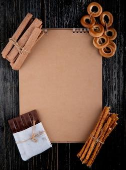 Vista superior copia espacio palitos de maíz con palitos de pan chocolate y rosquillas secas con un cuaderno sobre un fondo de madera negra