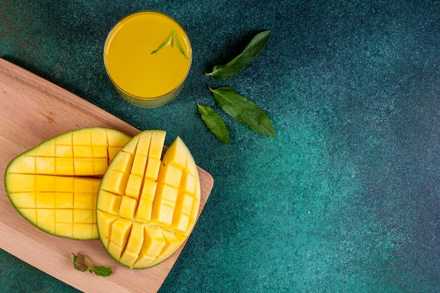 Vista superior copia espacio en rodajas de mango en la pizarra con un vaso de jugo de naranja y hojas de menta