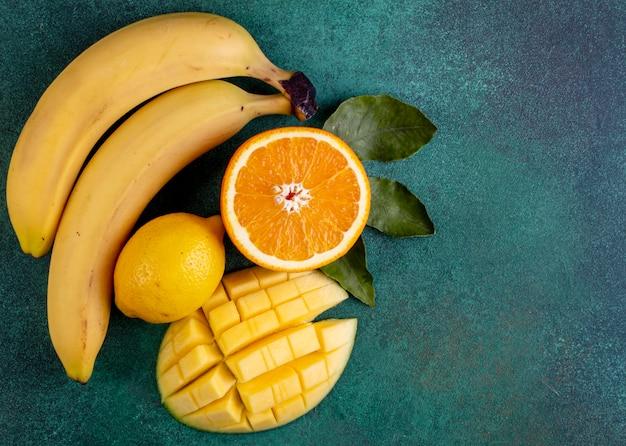 Vista superior copia espacio rodajas de mango con plátanos media naranja y limón en verde