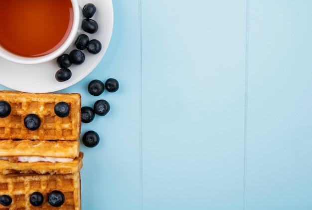 Vista superior copia espacio taza de arándanos de té con gofres sobre un fondo azul.