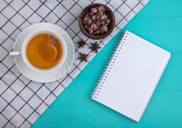 Vista superior copia espacio taza de té con una rodaja de limón y un cuaderno con flores secas sobre un fondo azul claro