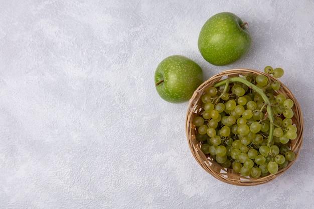 Vista superior copia espacio uvas verdes en una canasta con manzanas verdes sobre un fondo blanco.