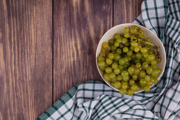 Vista superior copia espacio uvas verdes en un tazón sobre una toalla a cuadros verde en la pared de madera