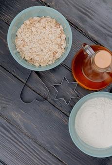 Vista superior de copos de avena con harina y mantequilla en la mesa de madera