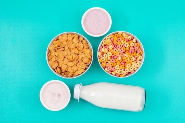Vista superior de copos de maíz y leche con yogurt en superficie azul horizontal