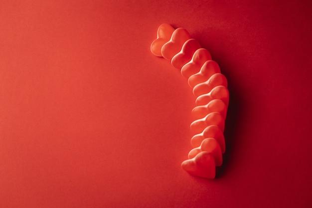 Vista superior del corazón en forma de goma en un fondo rojo
