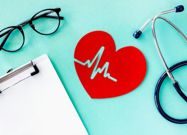 Vista superior del corazón de papel con latidos del corazón y estetoscopio
