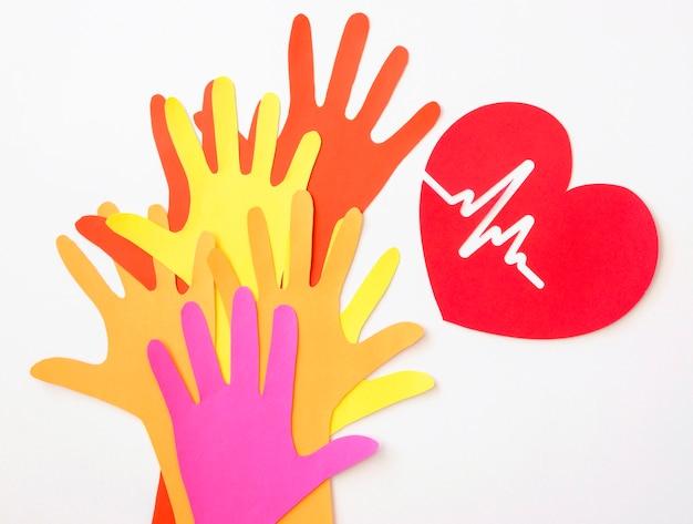 Vista superior del corazón de papel con latidos del corazón y manos