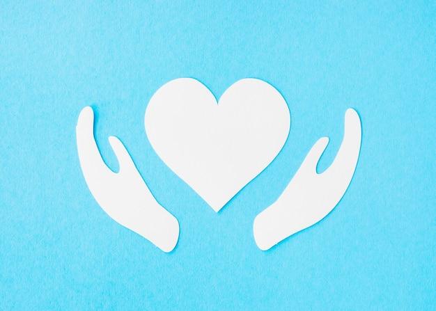 Vista superior del corazón de papel con manos de papel