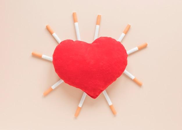 Vista superior corazón rodeado de cigarros
