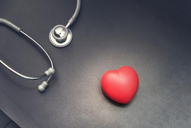En la vista superior, corazón rojo con equipo médico estetoscopio en el fondo del escritorio del doctor