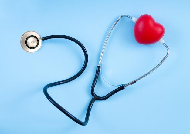 Vista superior de corazón rojo y estetoscopio sobre fondo azul. escuchar el concepto de latidos del corazón