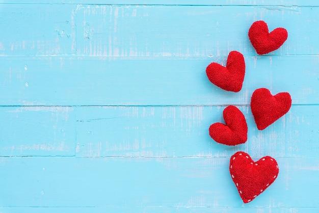 Vista superior del corazón rojo hecho a mano sobre fondo de madera de color azul y blanco