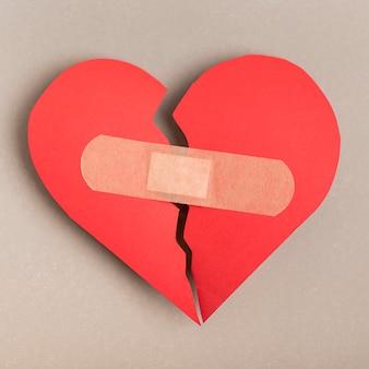 Vista superior del corazón roto con curita
