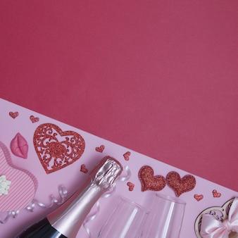 Vista superior de corazones, copas, champán, flores sobre un fondo rosa-rojo con espacio de copia, fecha del día de san valentín o concepto de fiesta