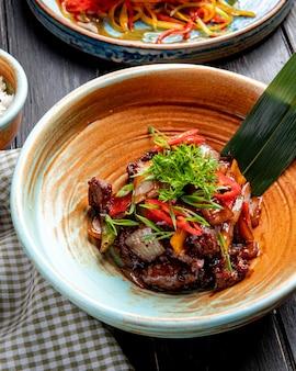 Vista superior de cordero asado con verduras y hierbas frescas y salsa en un plato sobre madera