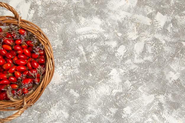 Vista superior de los cornejos amargos frescos dentro de la canasta en el escritorio blanco fruta berry vitamina agria suave planta árbol salvaje