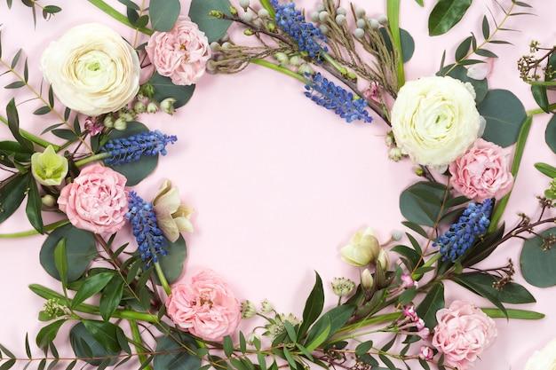 Vista superior de la corona de flores de marco redondo con rosas, ranúnculos, hojas, brotes, ramas aisladas sobre fondo blanco.