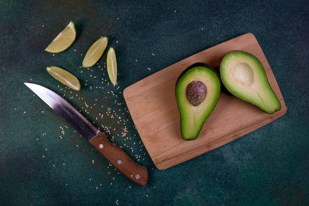 Vista superior cortada por la mitad aguacate en una pizarra con limón y cuchillo sobre un fondo verde oscuro