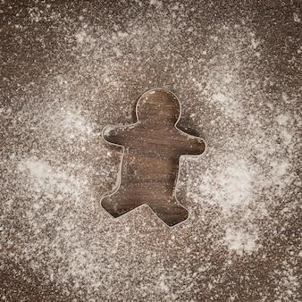 Vista superior cortador de galletas de hombre de jengibre con harina