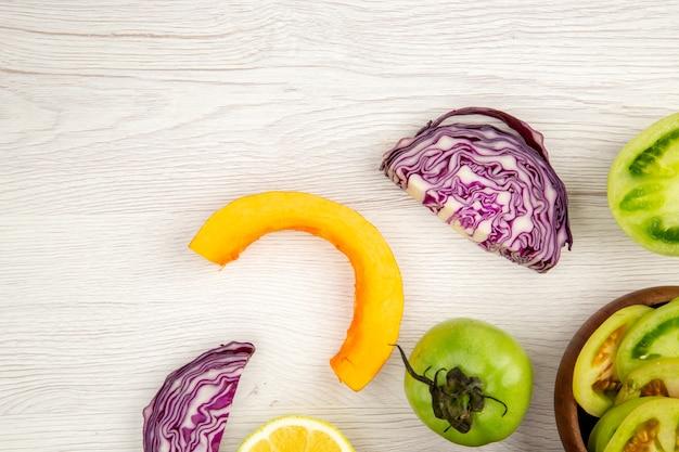 Vista superior cortar verduras repollo rojo tomate verde calabaza cebolla roja pimiento caulifower limón en tazones de madera sobre superficie de madera blanca lugar libre