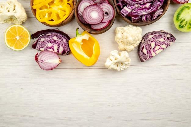 Vista superior cortar verduras repollo rojo tomate verde calabaza cebolla roja pimiento coliflor limón en tazones de madera en la mesa de madera blanca espacio libre