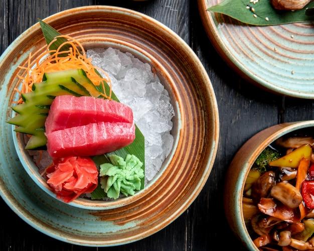 Vista superior de corte de rodaja de sashimi de atún con pepinos, jengibre y salsa de wasabi en cubitos de hielo en un recipiente en la mesa de madera