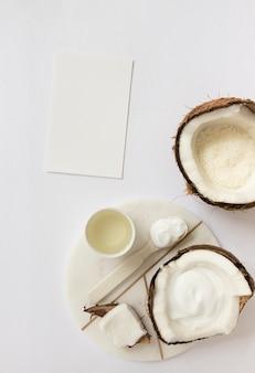 Vista superior de cosmética con coco y tarjeta en blanco sobre superficie blanca