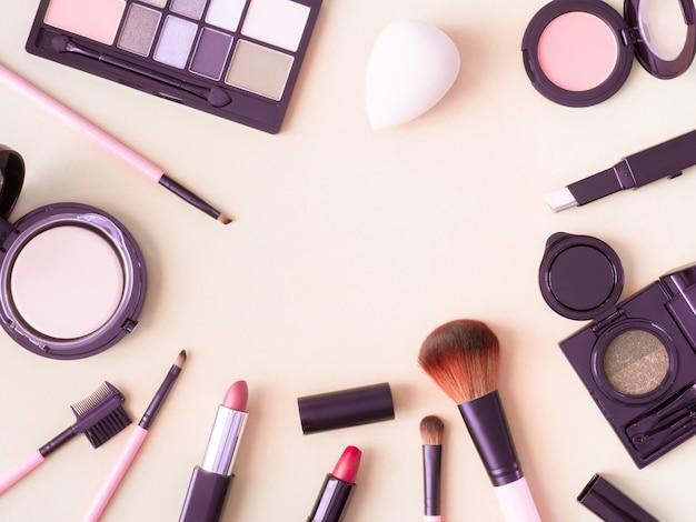 Vista superior de cosméticos con lápiz labial, productos de maquillaje, paleta de sombras de ojos