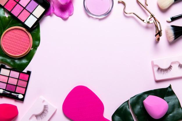 Vista superior de cosméticos sobre fondo rosa con espacio de copia