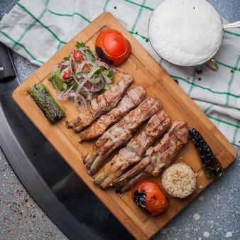 Vista superior costillas de kebab con verduras fritas y cebolla picada y ayran y cuchillo en tabla de cortar