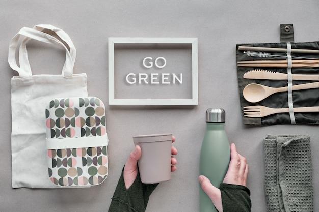 Vista superior creativa, concepto de almuerzo lleno de basura cero. juego de almuerzo plano: cubiertos de bambú, lonchera, bolsa de algodón y mano con taza de café para llevar en papel artesanal. marco con el texto