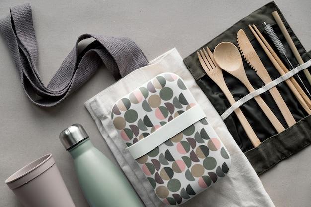 Vista superior creativa, kit de almuerzo sin desperdicios, caja de almuerzo para llevar en bolsa de algodón, organizador de cubiertos de bambú, caja reutilizable y taza de café para llevar. estilo de vida sostenible, diseño plano en papel artesanal.