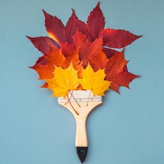 Vista superior creativa plana composición de concepto de otoño. pincel seco brillante hojas de otoño fondo de papel copia espacio plantilla cuadrada simulacro otoño tarjetas de invitación de aniversario de boda de acción de gracias