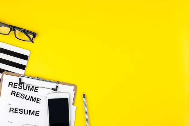 Vista superior creativa plana del escritorio con espacio de copia de documentos de currículum sobre fondo amarillo audaz en estilo minimalista.