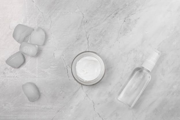 Vista superior de crema y botella sobre fondo de mármol