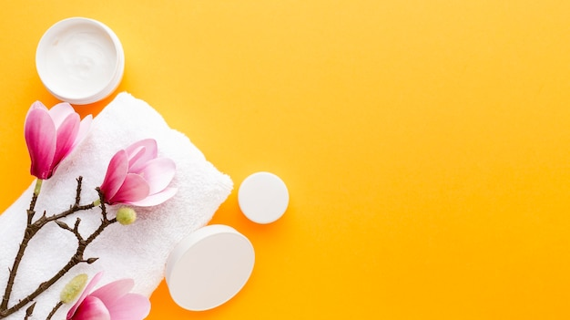 Vista superior crema cosmética con flores