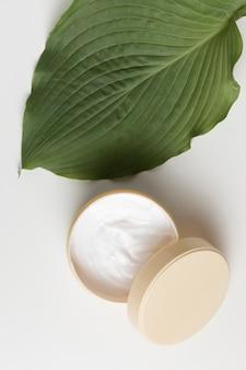 Vista superior de una crema y hojas con fondo blanco.