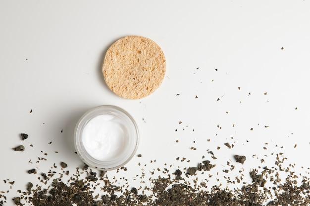 Vista superior de crema natural y hierbas sobre fondo blanco.
