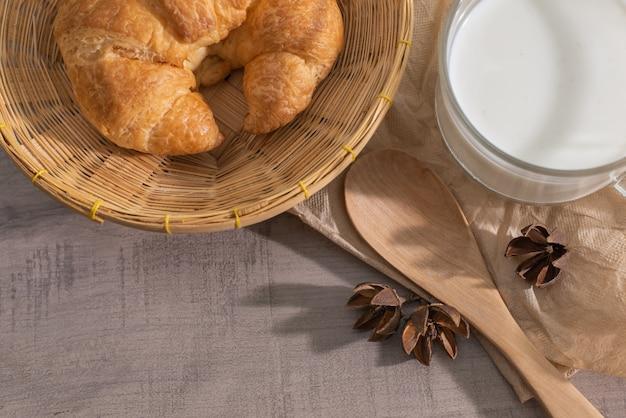 Vista superior de croissant en la cesta, una taza de leche, cuchara de madera