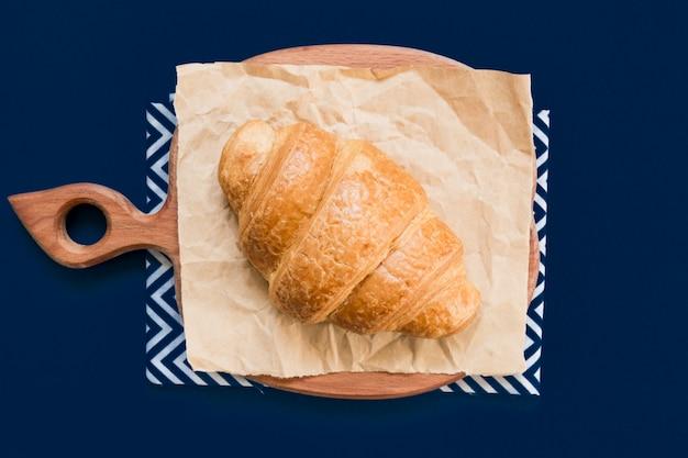 Vista superior del croissant en tabla de cortar y papel artesanal sobre fondo azul con espacio de copia.