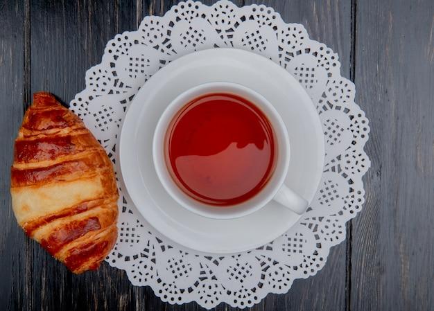 Vista superior de croissant y una taza de té en bolsita de té en papel tapete y fondo de madera