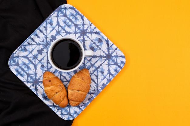 Vista superior de croissants con café con copia espacio sobre fondo negro y amarillo horizontal