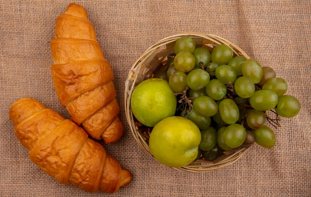 Vista superior de croissants y canasta de uva y pluots sobre fondo de tela de saco