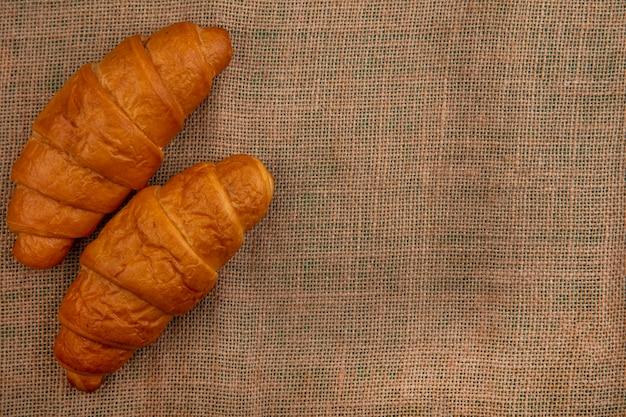 Vista superior de croissants sobre fondo de tela de saco con espacio de copia