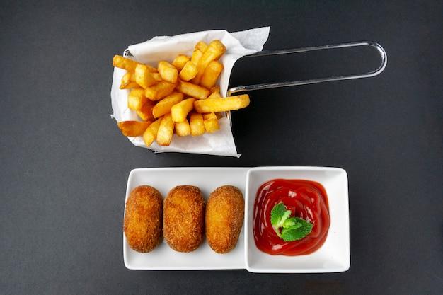 Vista superior de croquetas con patatas fritas y tomate frito.