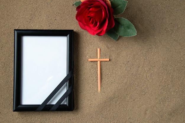 Vista superior de la cruz de palo con flor roja y marco de imagen en la arena muerte funeral palestina