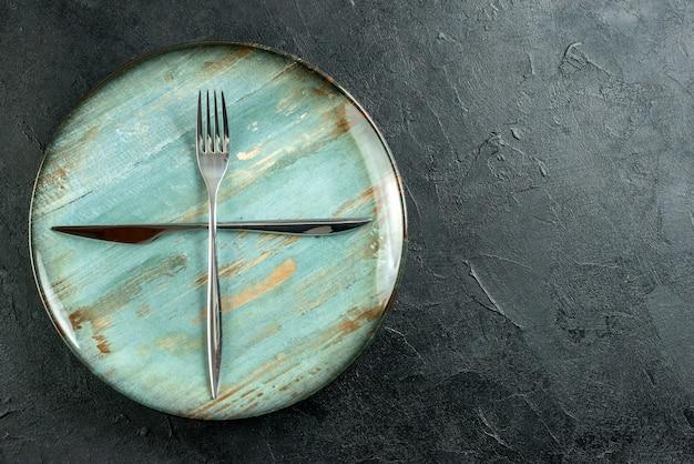 Vista superior cruzada tenedor y cuchillo en placa redonda cian en lugar de copia de mesa oscura