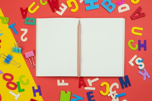 Vista superior del cuaderno abierto en blanco con lápiz y alfabetos